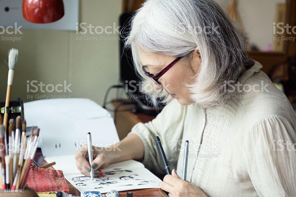 Asian senior woman artist sketching stock photo