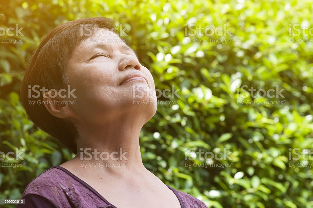 Asian senior woman relaxing and breathing fresh air. stock photo
