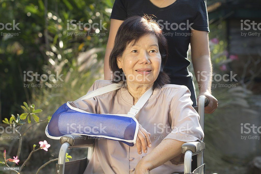 Asian senior woman with broken wrist on wheel chair royalty-free stock photo