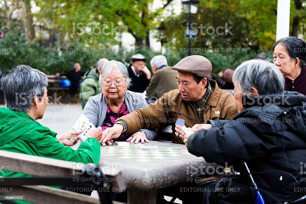 NYC Asian Seniors Gather Outside in Chinatown to Play Cards stock photo