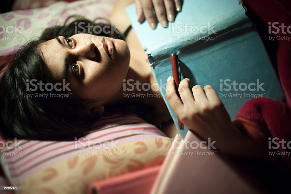 Asian serene girl thinking and lying on bed with book. stock photo