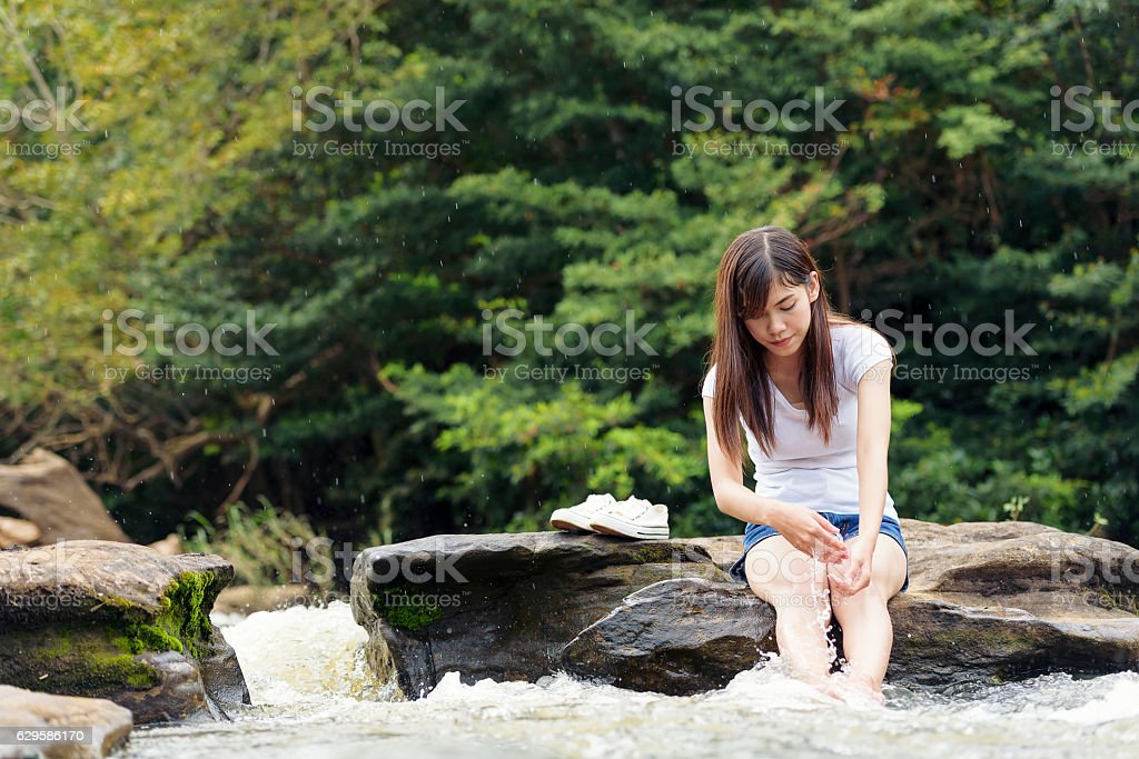 Asian sexy woman sitting on the stone splatter in cascade stock photo