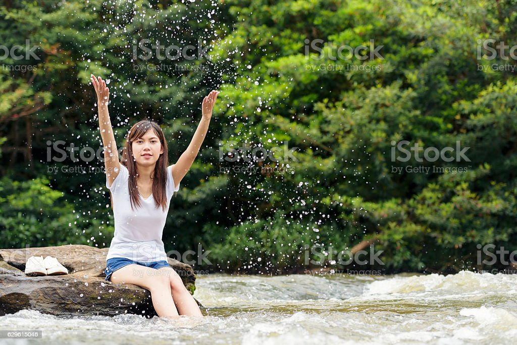 Asian sexy woman sitting on the stone splatter in cascade, stock photo