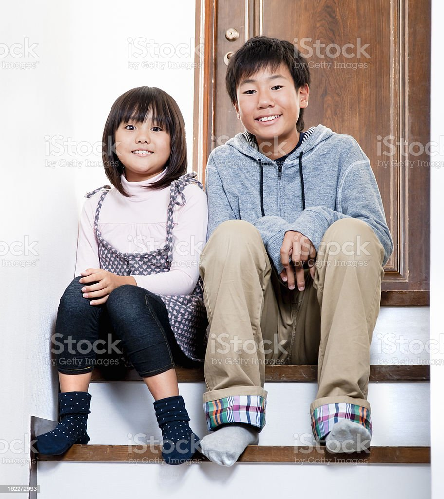 Asian siblings, sitting on stairs stock photo