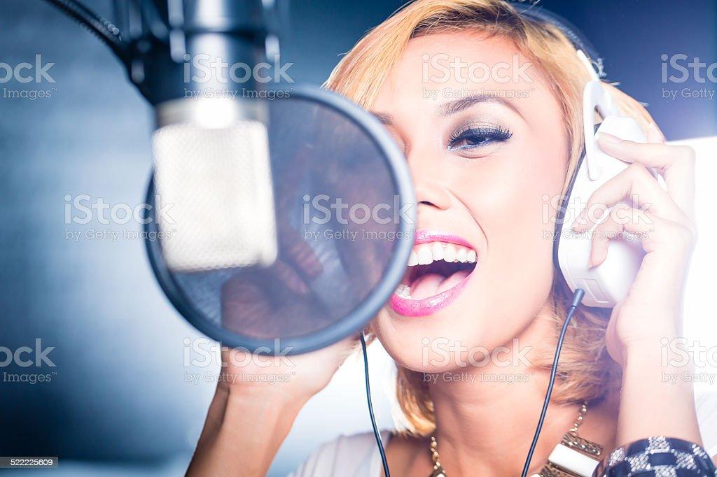 Asian singer producing song in recording studio stock photo
