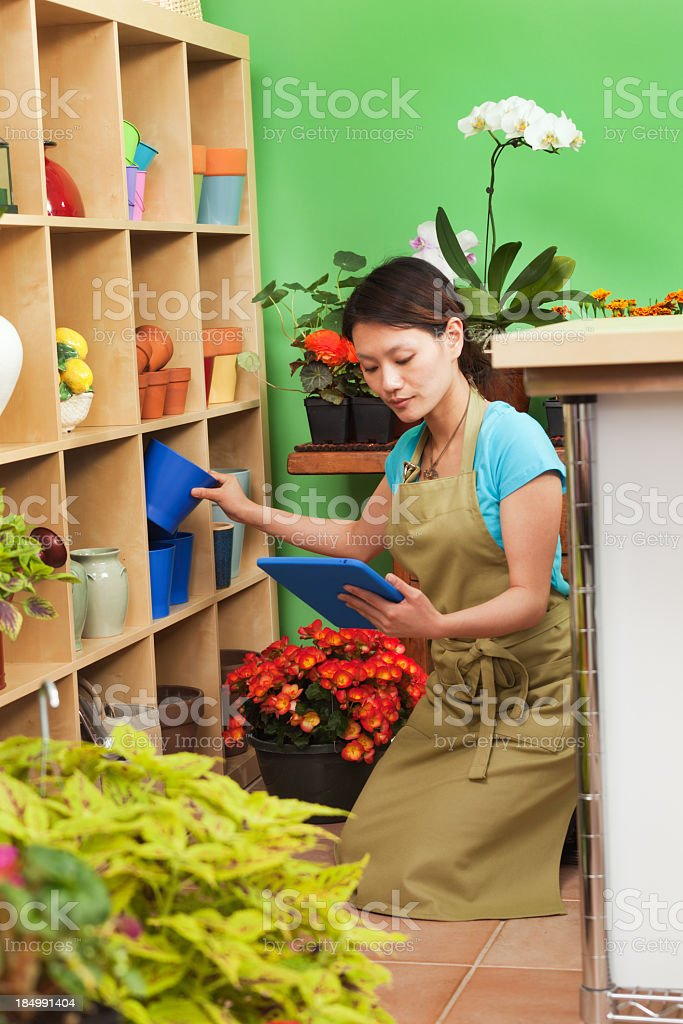 Asian Small Retail Business Flower Shop Worker Doing Inventory royalty-free stock photo