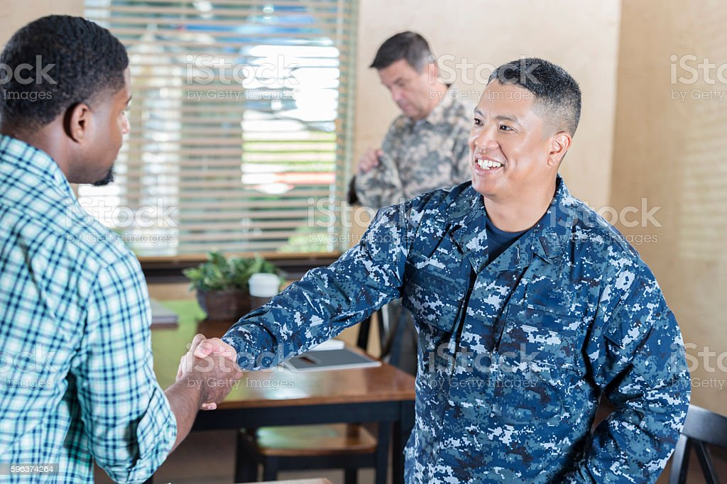 Asian soldier  meeting man in military recruitment office stock photo