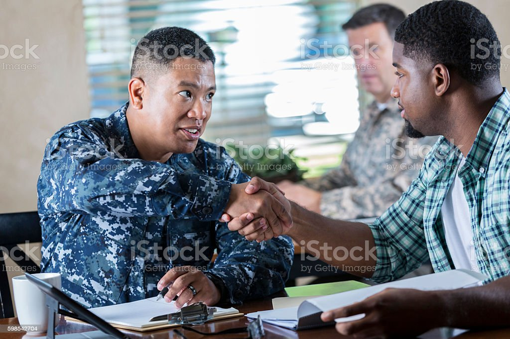 Asian soldier meeting with young man at military recruitment event stock photo