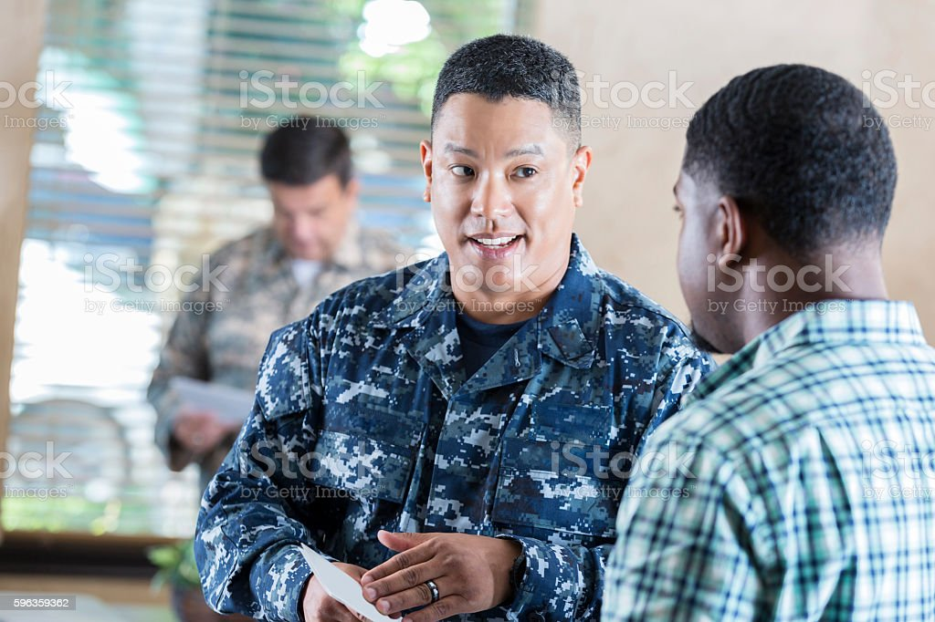 Asian soldier recruiting young man in military office stock photo