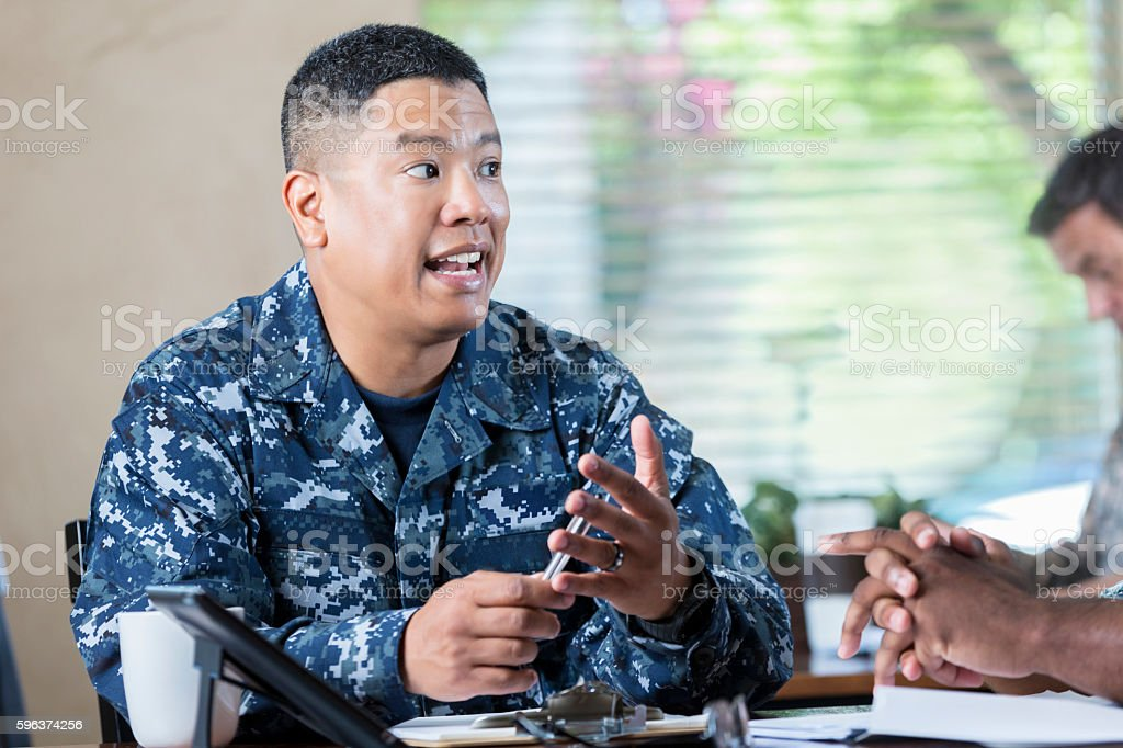 Asian soldier talking to  man during military recruitment event stock photo