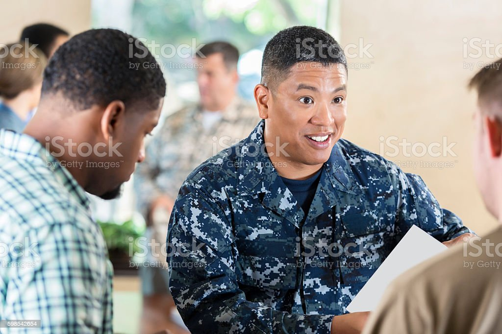 Asian soldier talking to young man at military recruitment event stock photo