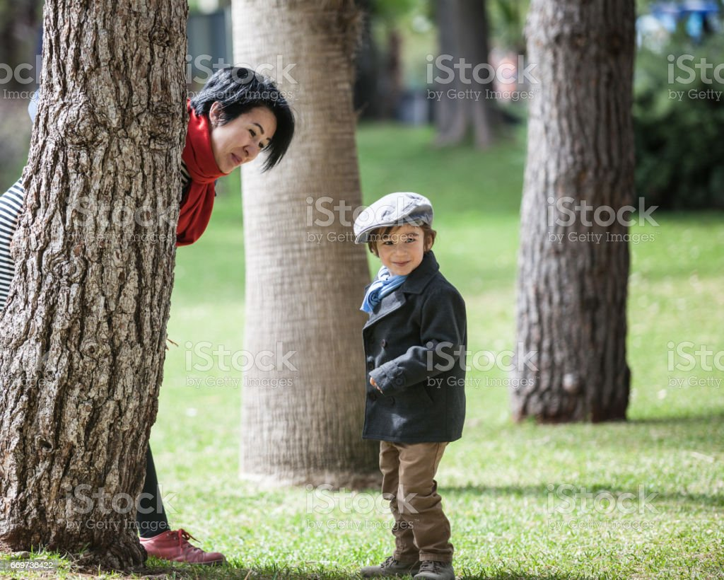 Asian Son And Mother Playing In Green Public Park stock photo