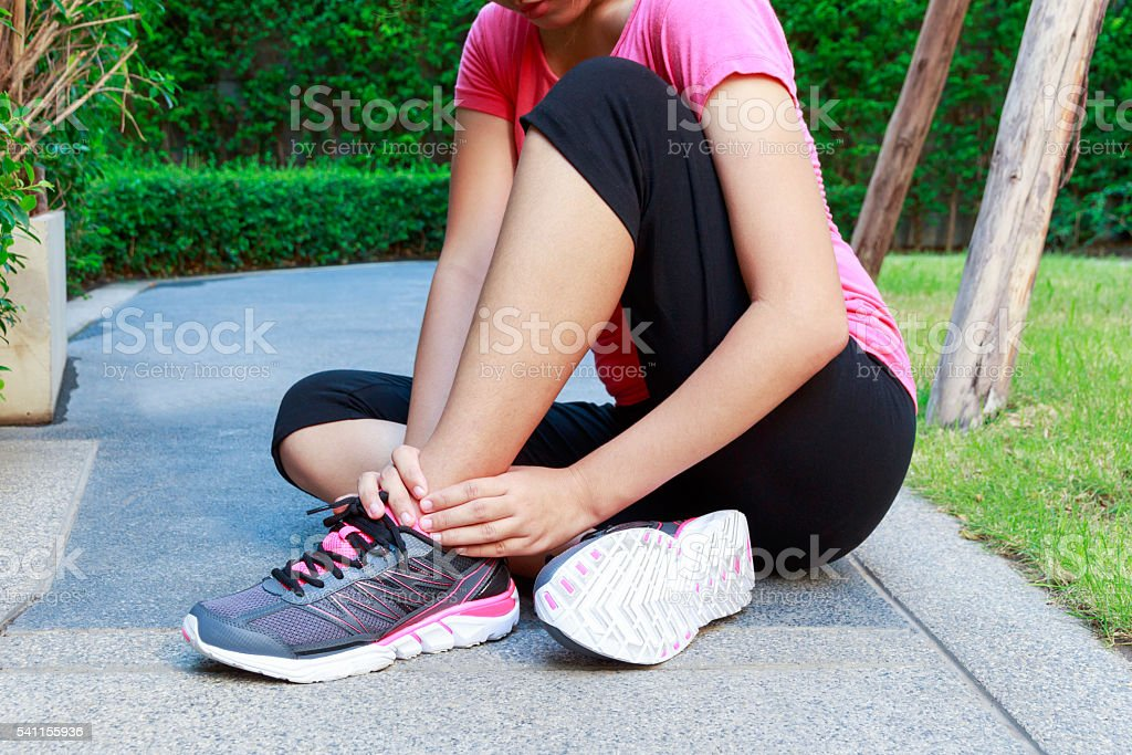 Asian sporty woman ankle sprain while jogging or running stock photo