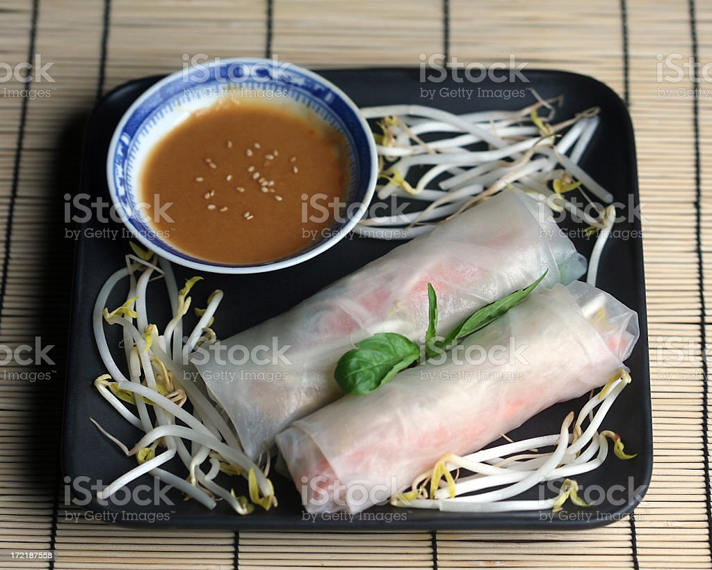 Asian spring rolls, bean sprouts, basil,  peanut sauce, sesame seeds royalty-free stock photo