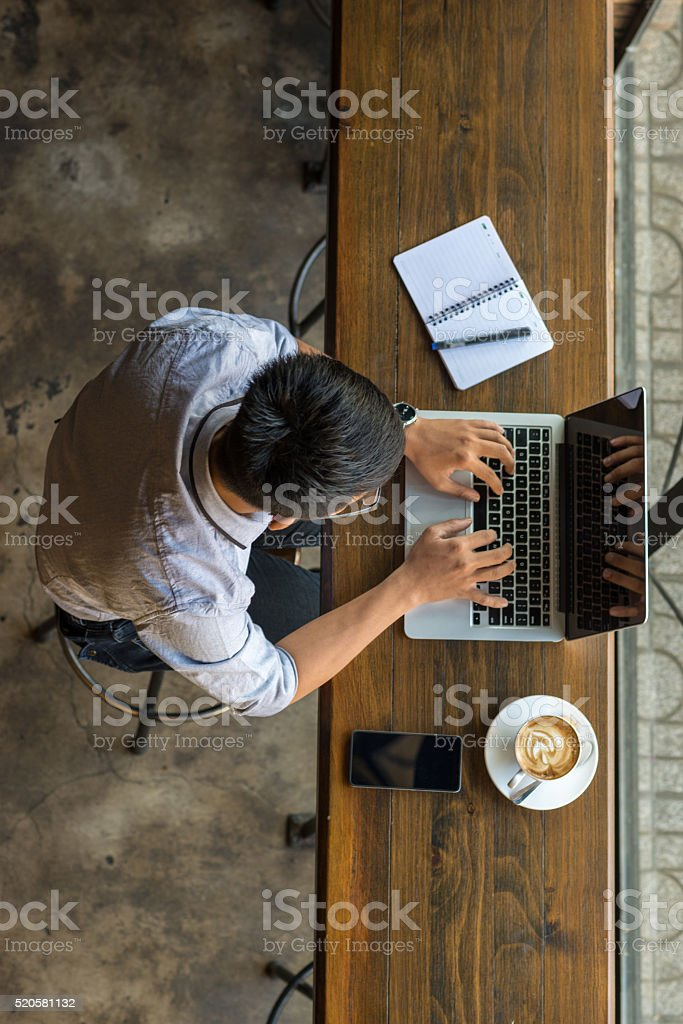Asian student chatting with online friends on laptop stock photo