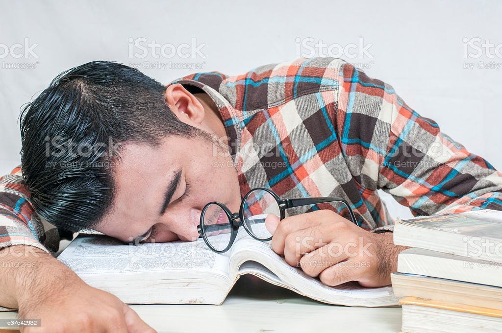 Asian student lying and sleeping on the school desk stock photo