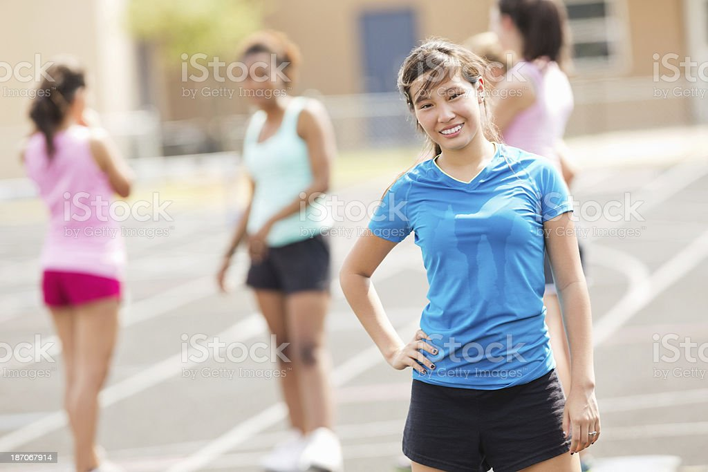 Asian student on track with classmates during athletics class royalty-free stock photo