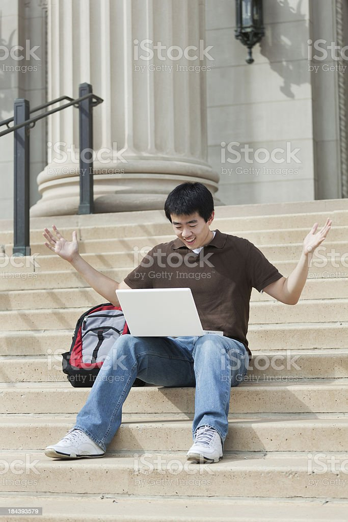 Asian Student Receiving Good News from Laptop on University Campus royalty-free stock photo
