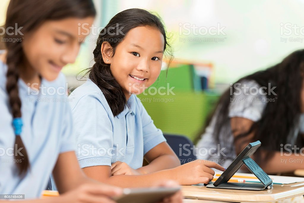 Asian student smiles at camera in classroom with digital tablet stock photo