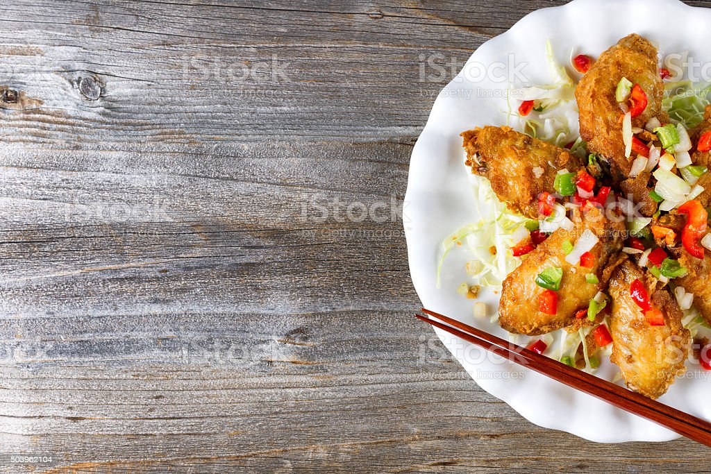 Asian style chicken wings on rustic wooded boards stock photo