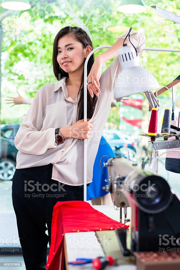 Asian tainlor or fashion designer leans on sewing desk stock photo