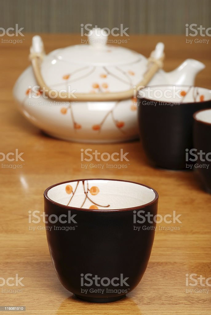 asian tea cup with pot in the background royalty-free stock photo