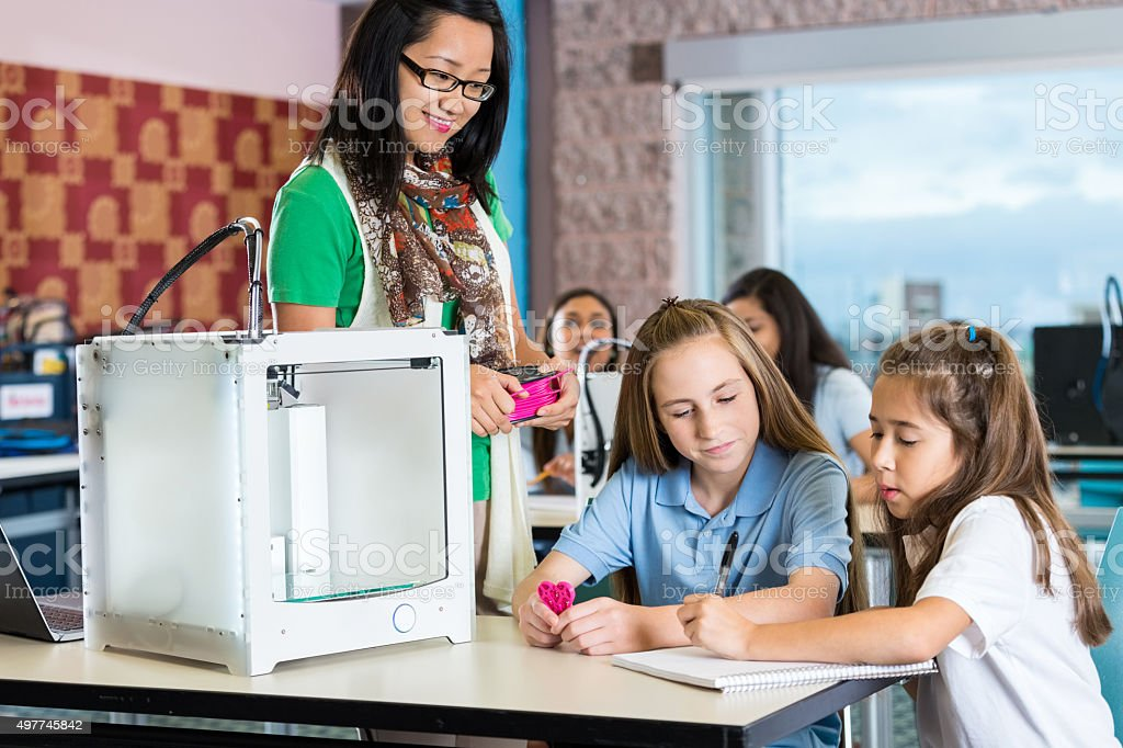 Asian teacher helping elementary students in 3D printing technology class stock photo