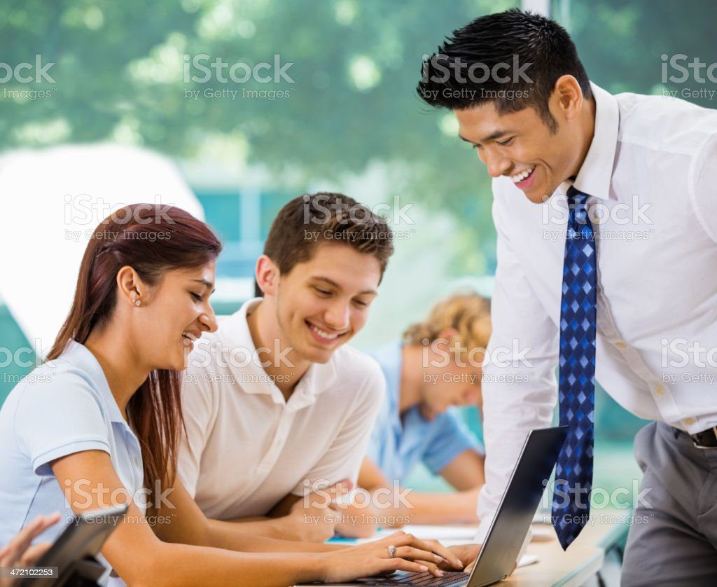 Asian teacher helping students with laptop at private school royalty-free stock photo