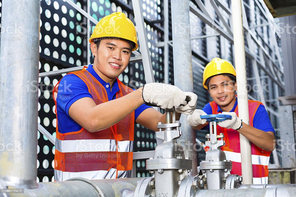 Asian Technicians or engineers working on valve royalty-free stock photo