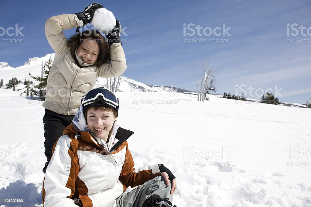 Asian Teenage Girl Hitting Young Woman with Snowball on Mountain royalty-free stock photo