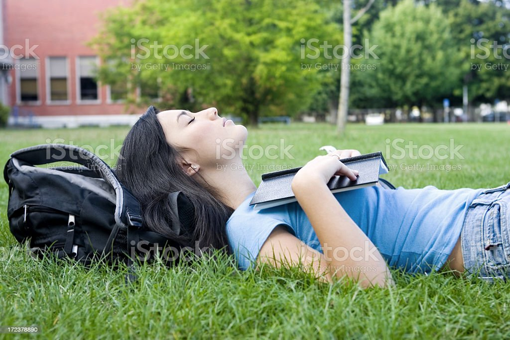 Asian Teenage Girl Lying on High School Campus Grass, Copyspace royalty-free stock photo