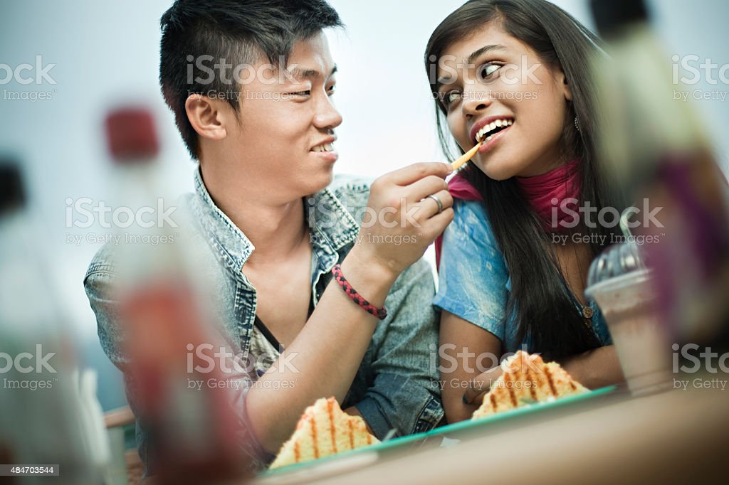 Asian teenage lovers of different ethnicity enjoying food at restaurant. stock photo