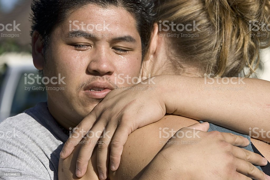 Asian Teenage Man Hugging Blond Girl, Crying royalty-free stock photo