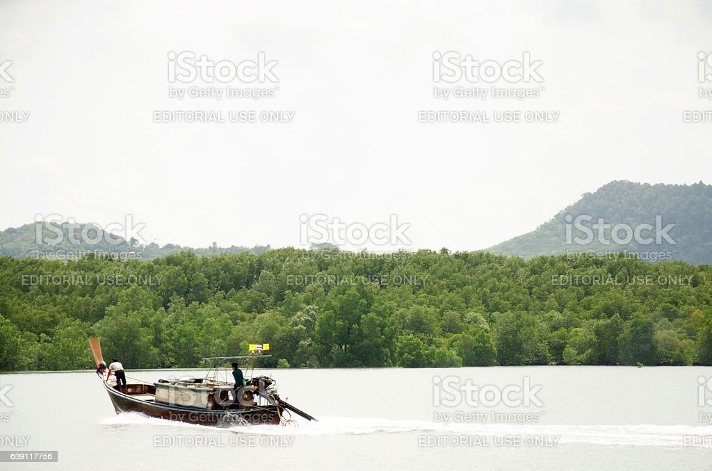 Asian thai people driving wooden motor boat on the sea stock photo