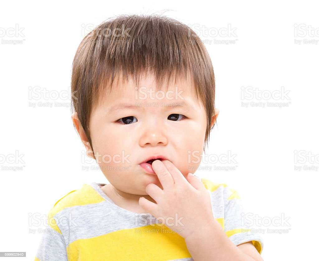 Asian toddler sucking fingers stock photo
