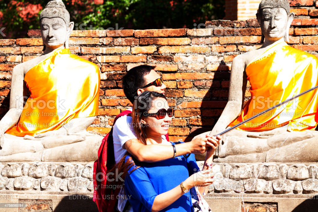 Asian tourist couple taking selfie in Wat Yai Chai Mongkol stock photo