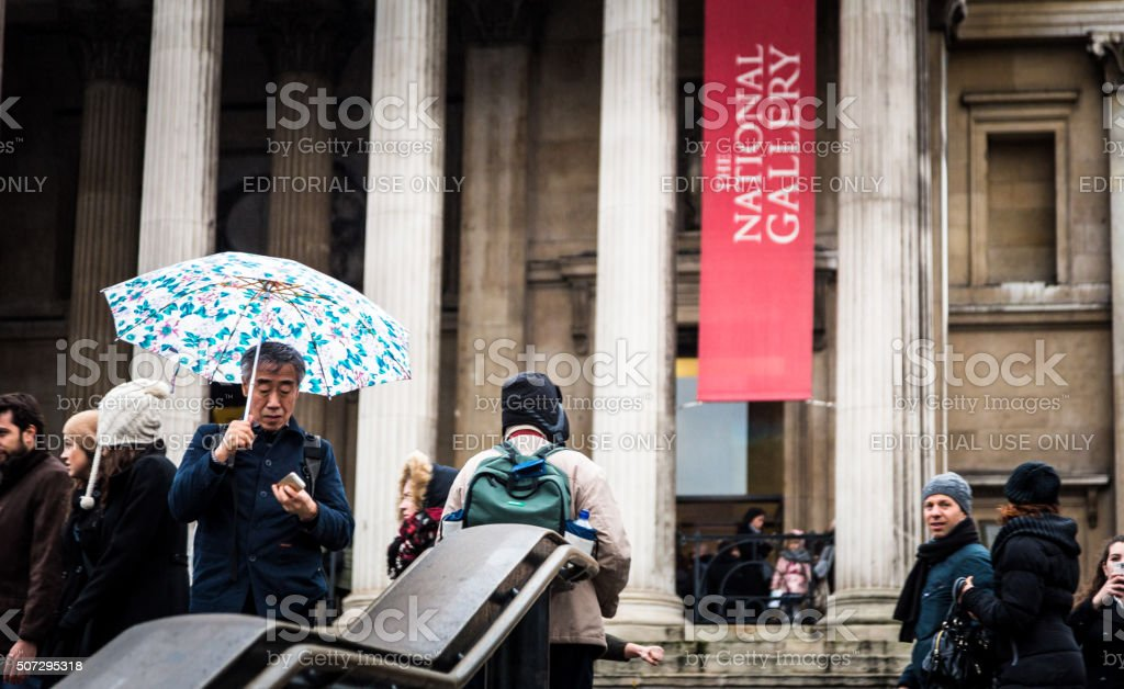 Asian tourist looking at smartphone, National Gallery, London, UK stock photo
