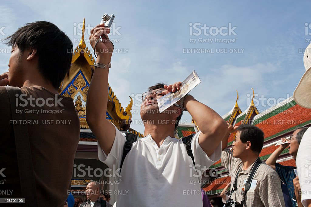 Asian tourists photographing at the Grand Palace, Bangkok, Thailand. stock photo