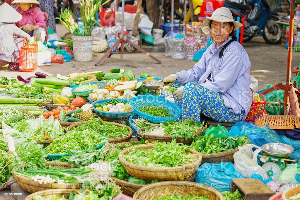Asian trader selling fresh vegetables and green garden stuff stock photo