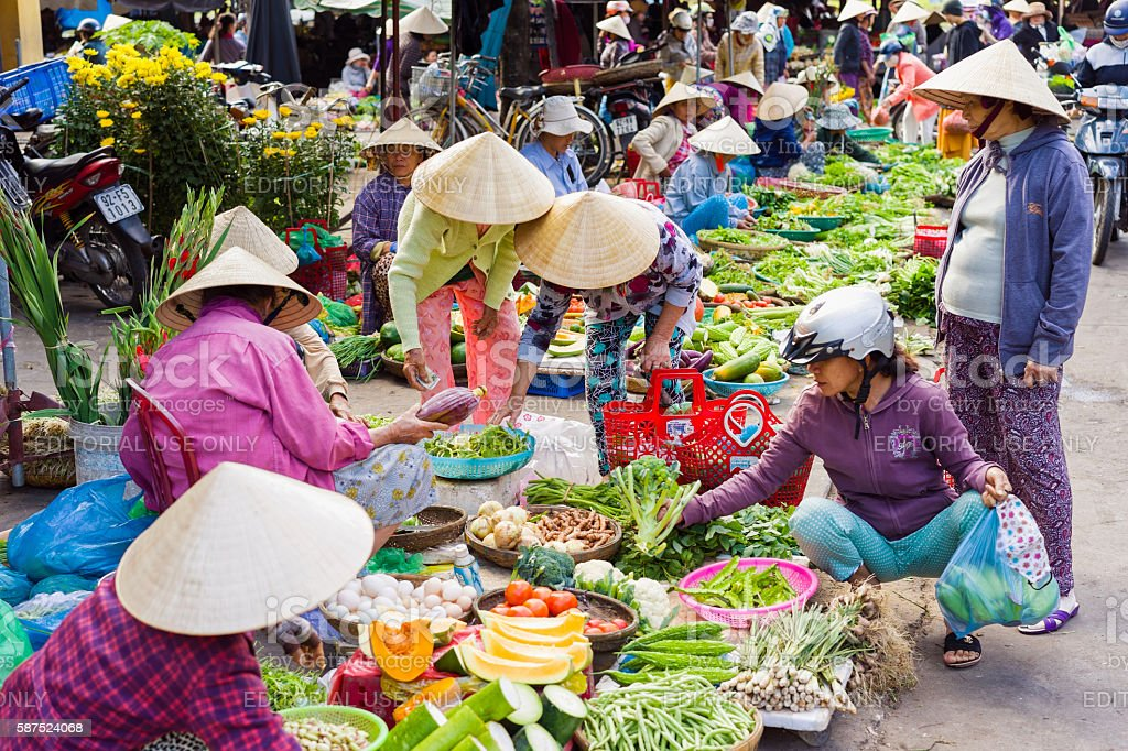 Asian traders selling fresh vegetables in the street market stock photo