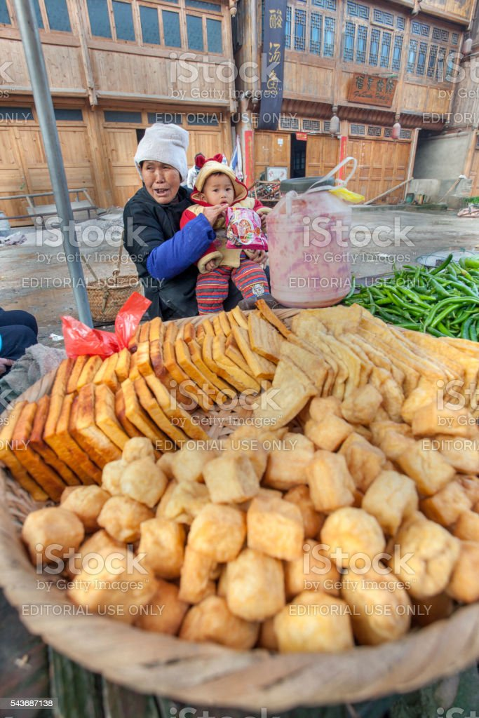 Asian tradeswoman selling fried tofu in the Chinese countryside. stock photo