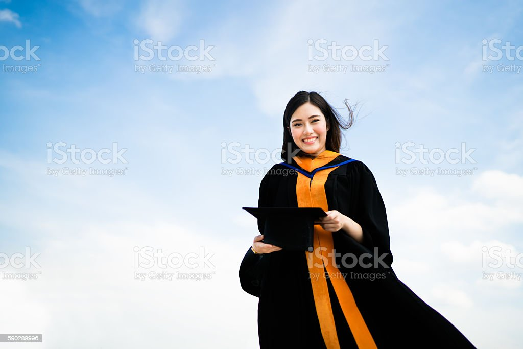 Asian university graduate student woman smiling in graduation academic dress stock photo