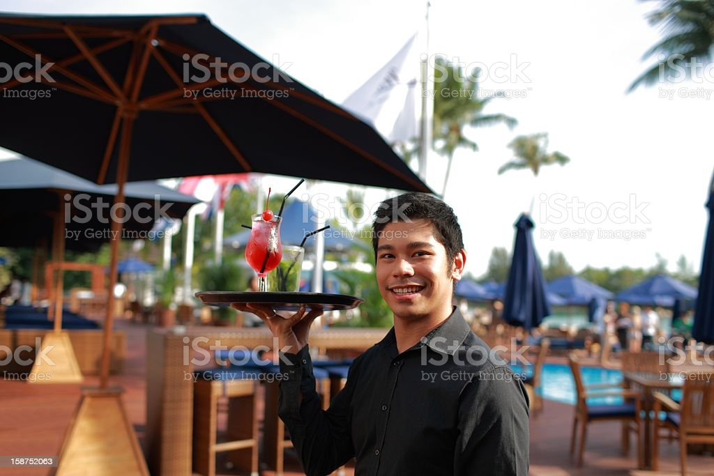 Asian waiter serving drinks by the pool royalty-free stock photo