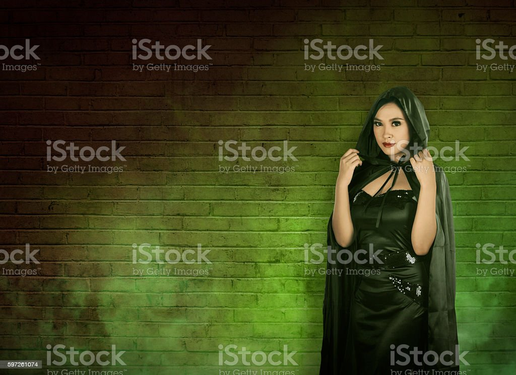 Asian witch woman in empty room with green fog. stock photo