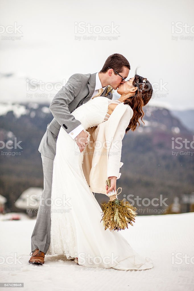 Asian Woman and Caucasian Man Wedding in Snow Mountains stock photo