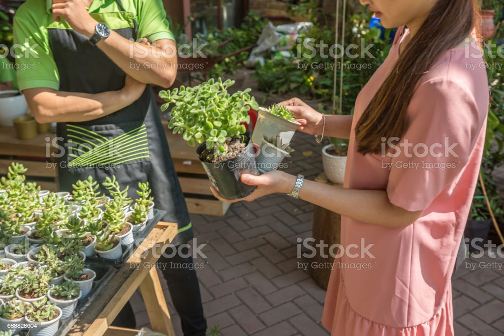 Asian woman ask the gardener about some new plants in the garden