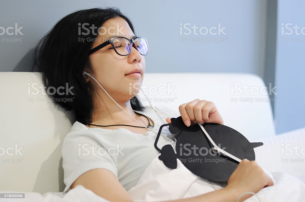 Asian woman be sleep and smile with alarm clock stock photo