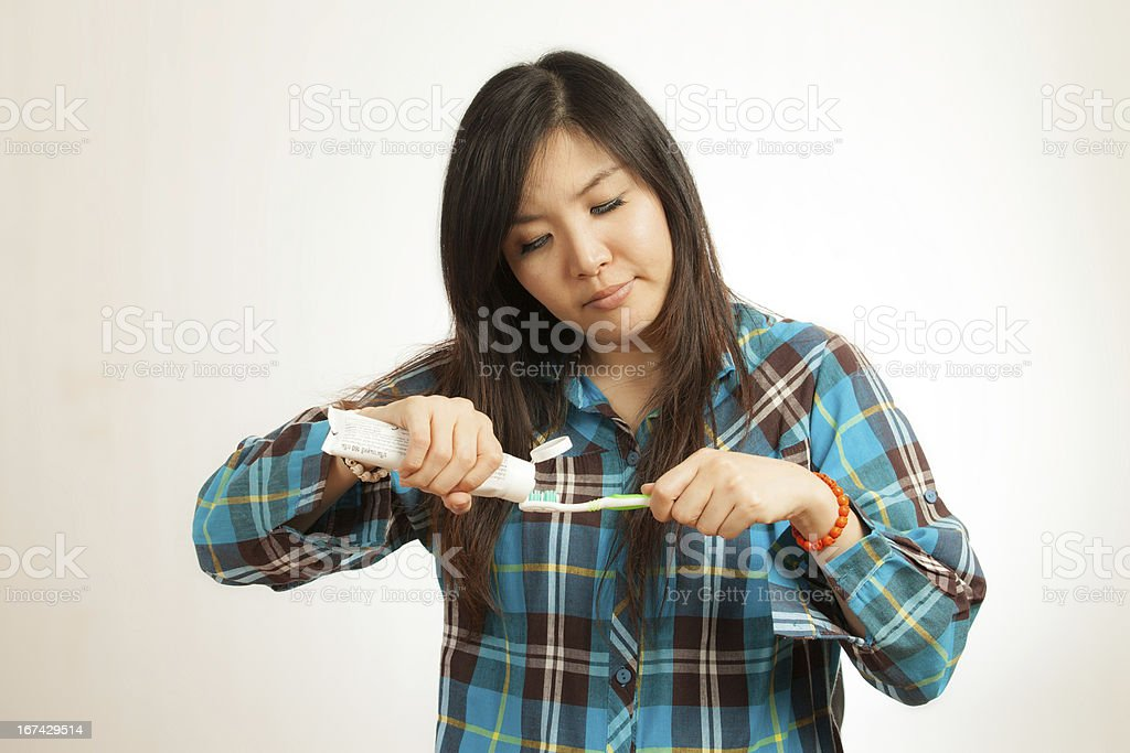Asian woman brushing her teeth royalty-free stock photo