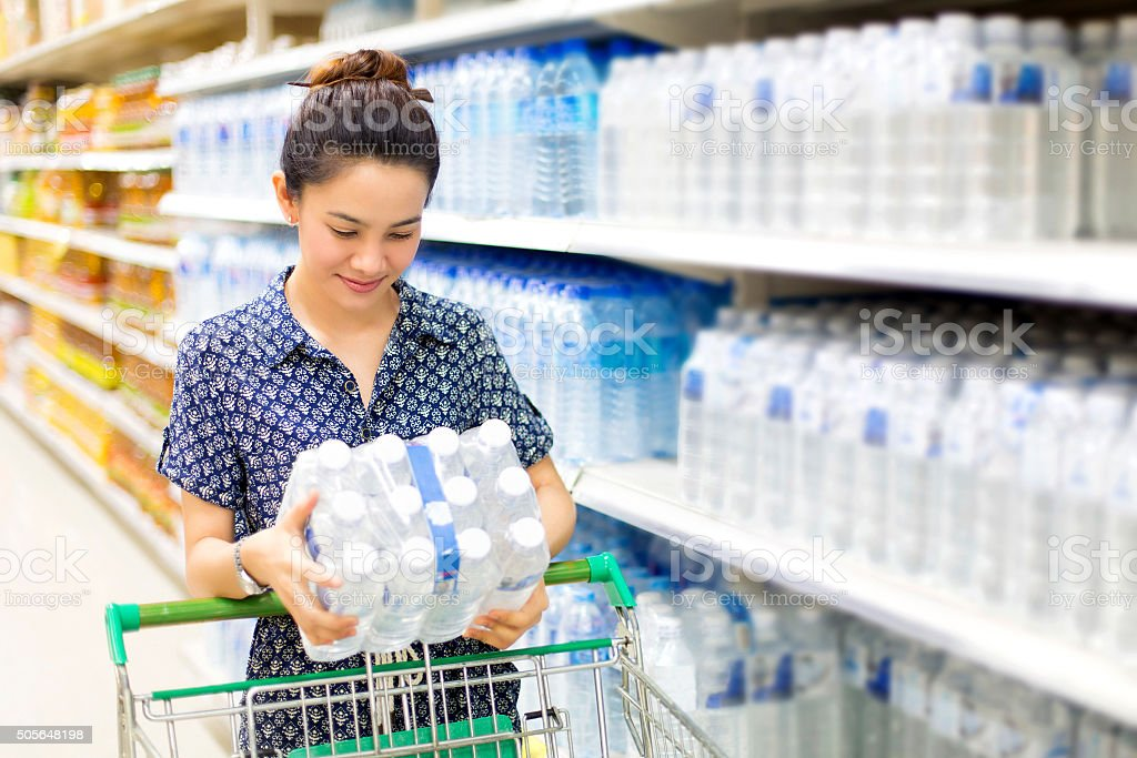 Asian woman buys in the supermarket bottle of water stock photo