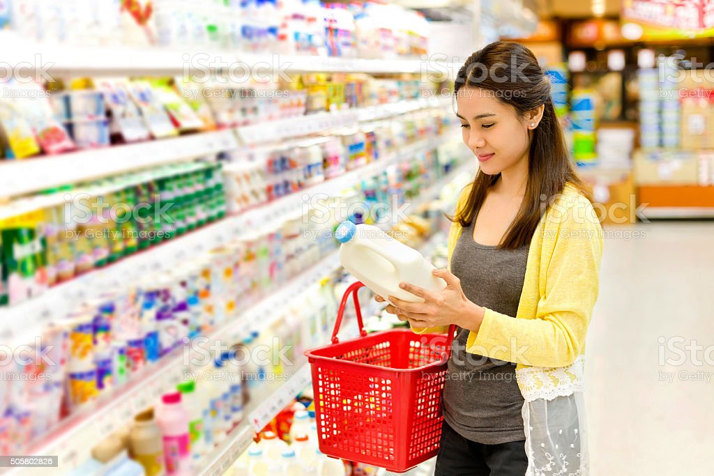 Asian woman buys in the supermarket gallon of milk stock photo